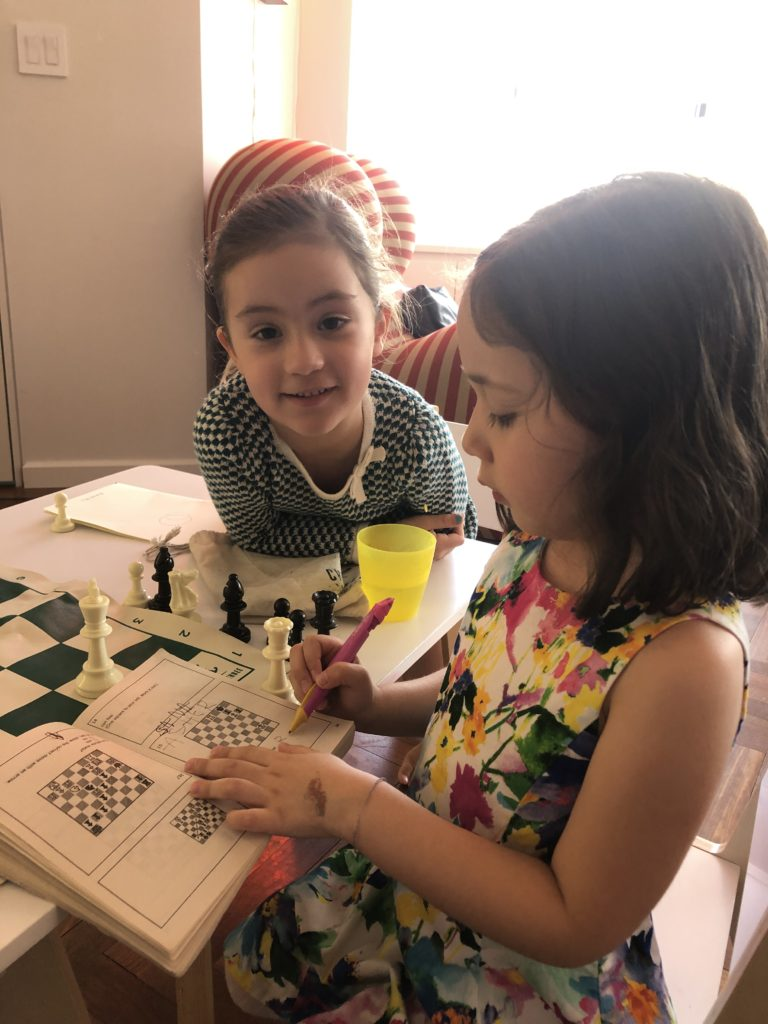 Kids doing a chess puzzle